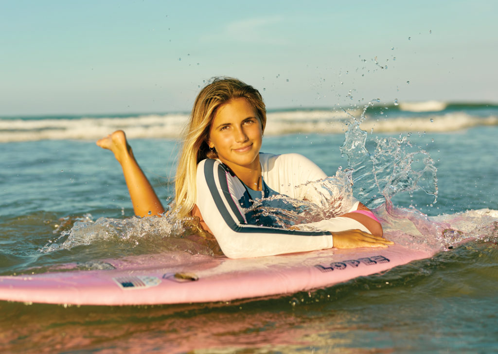 Zoe Benedetto relaxing on her surfboard