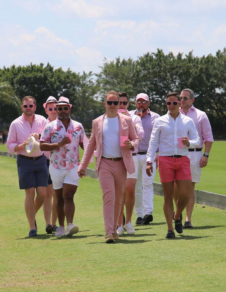 A crowd of people walking around the field at the Gay Polo Tournament