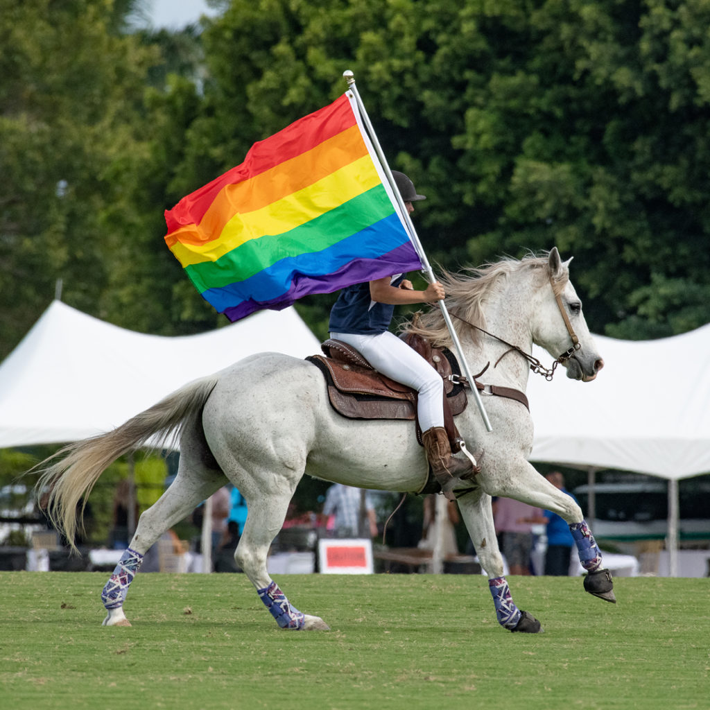 Jockey riding a horse carrying a gay pride flag