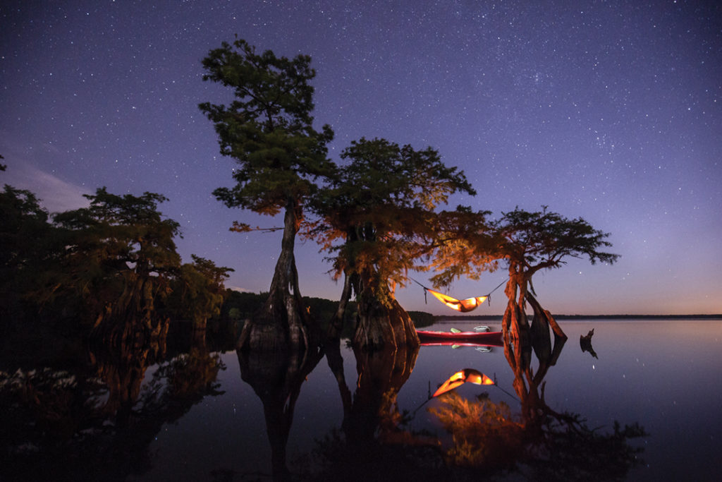 Image of a man in a lighted hammock underneath a tree on a lake