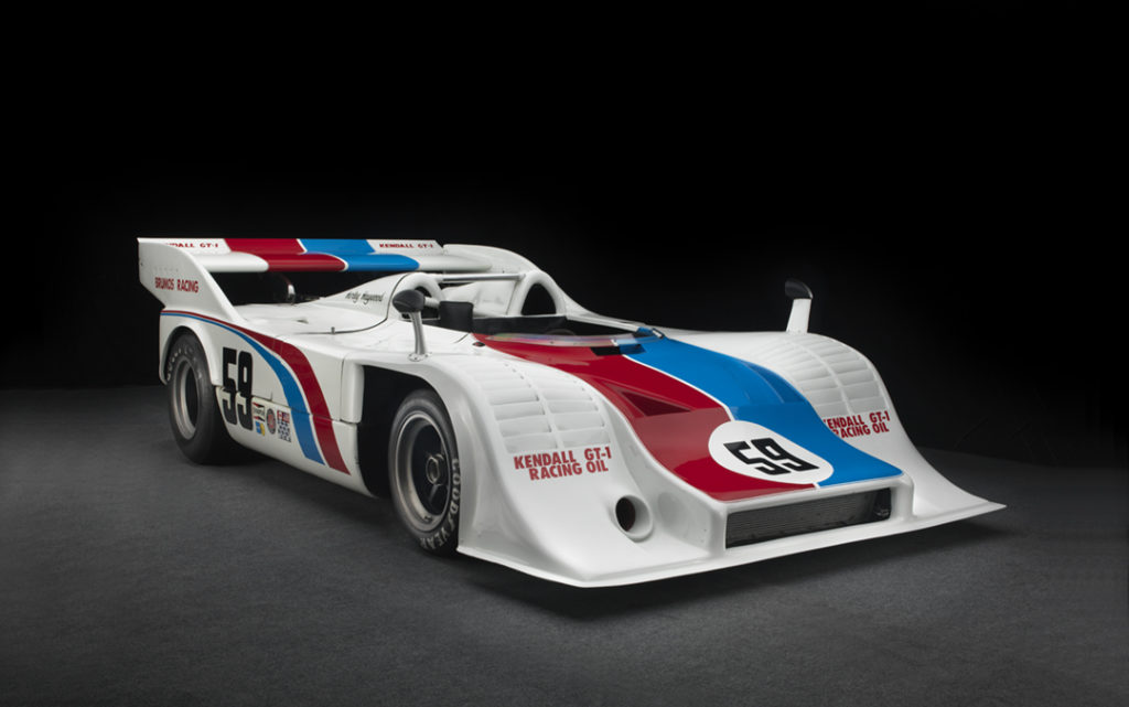 The white car has a 59 on the side and front and a blue and red strip stretching from the back to the front.