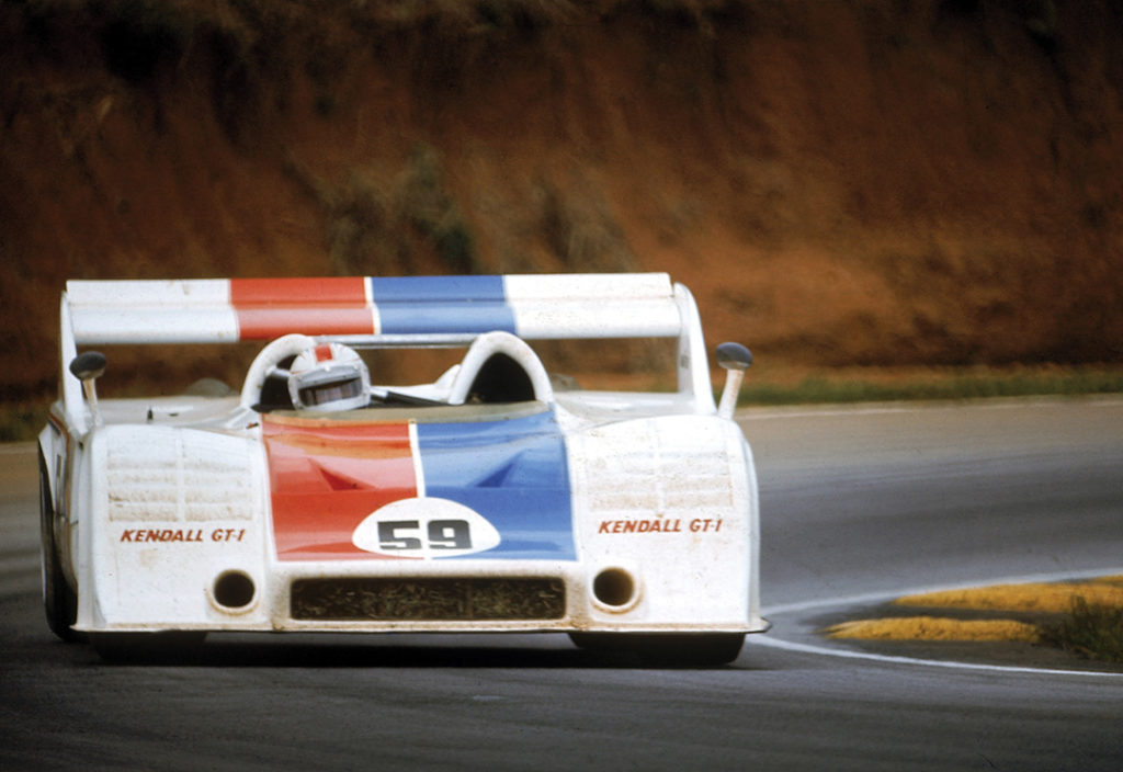 Haywood behind the wheel of a 917-10 Porsche Spyder, a low, boxy car. It is white with a blue and red stripe.