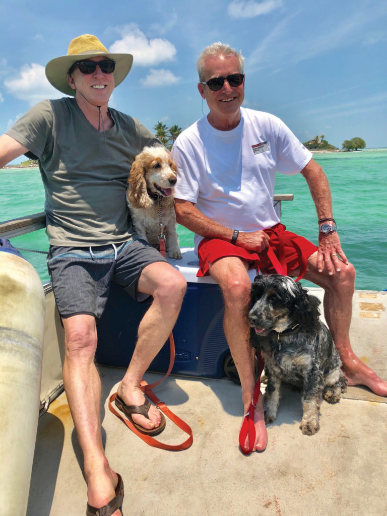 Haywood and his husband and their two dogs smile on a boat. Water is visible in the background.