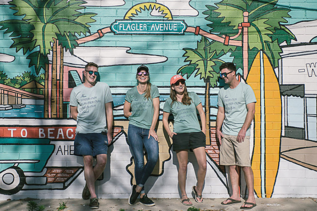 Small business owners standing in front of a mural.