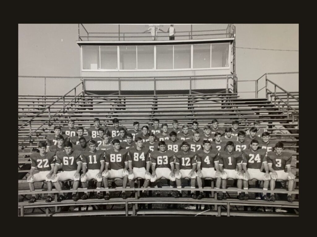 Leonard George is visible in the second row of this Jesuit High School team photo taken on the bleachers. He is the only Black player in the black and white photo.