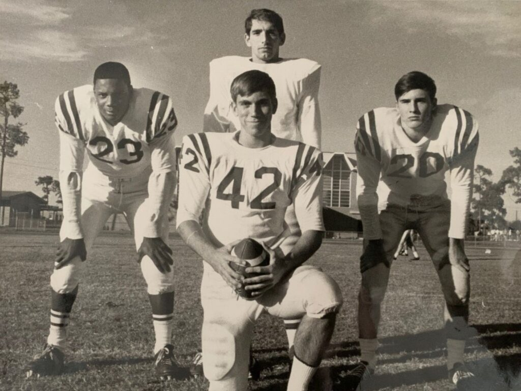 Leonard George, who is Black, crouches with his hands on his knees alongside three white teammates. They all are in football uniforms. George is number 23.