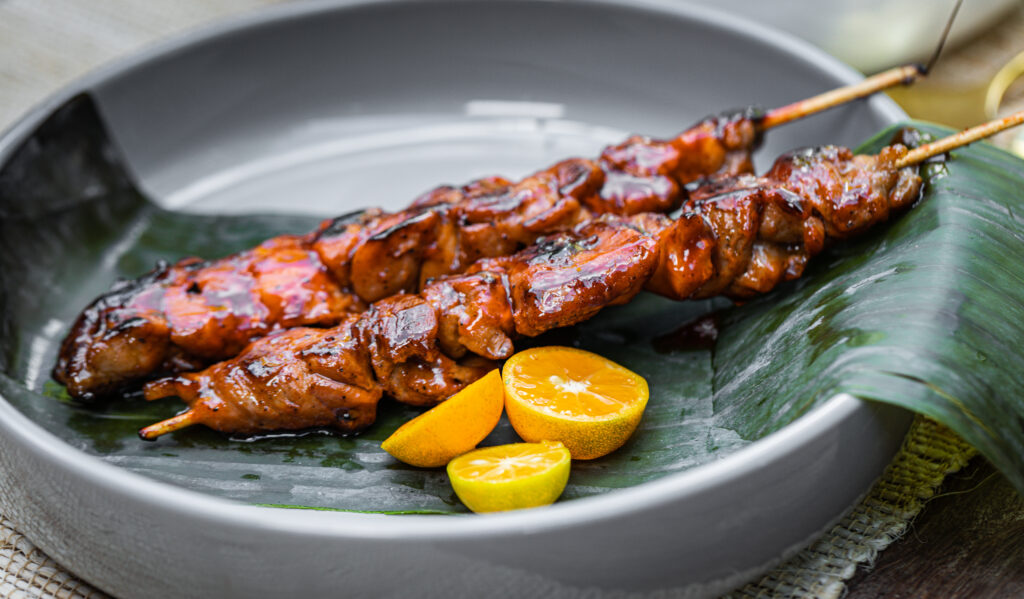 Two kebabs in a gray dish with a citrus garnish and resting on a banana leaf.