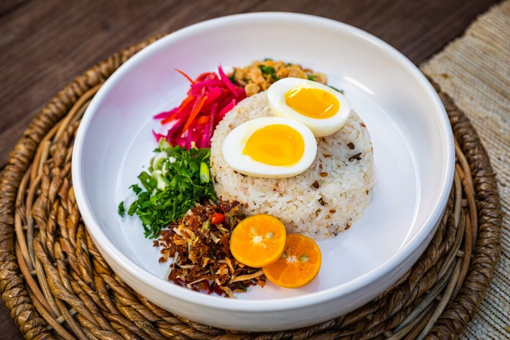 A dish with rice, garnishes and a hard boiled egg.