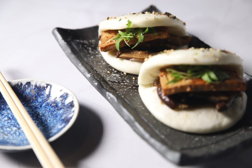 Two duck bao buns from Takato, one of the hottest South Florida restaurants. There is two wooden chopsticks resting on the side.
