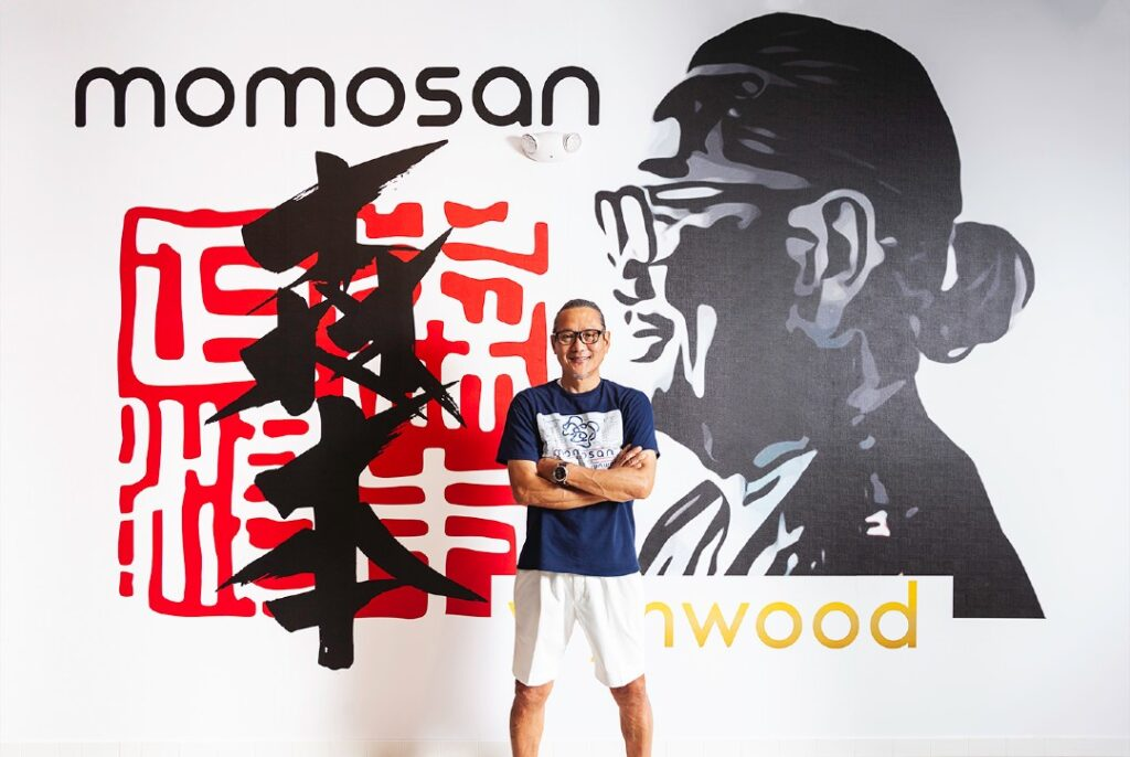 Masaharu Morimoto smiles with his arms crossed in front a wall with his picture and words reading mimosan wynwood.