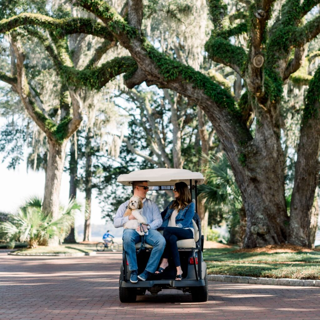 Montage Palmetto Bluff guests and their dog sit in the back of a gold cart under a large tree.