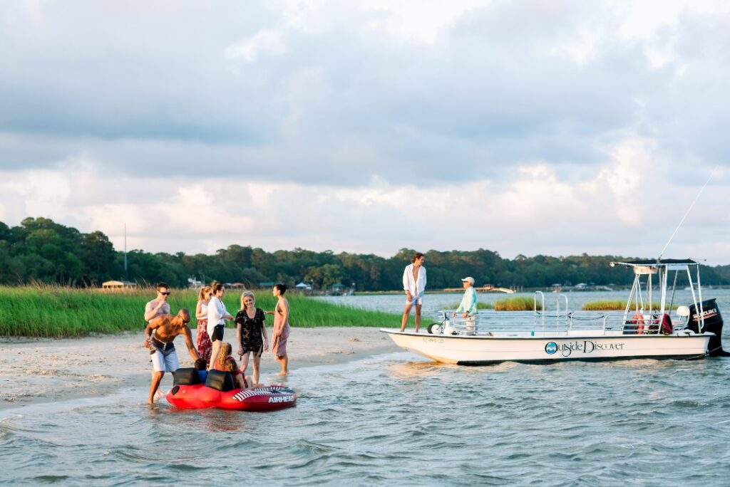 At Montage Palmetto Bluff, guest gather on the shore. A boat floats nearby and kids are in a race car themed tube.