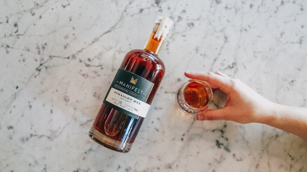An image of a bottle of rye whiskey with a hand holding a glass. It's the ingredient you need to make this twist on the whiskey sour.