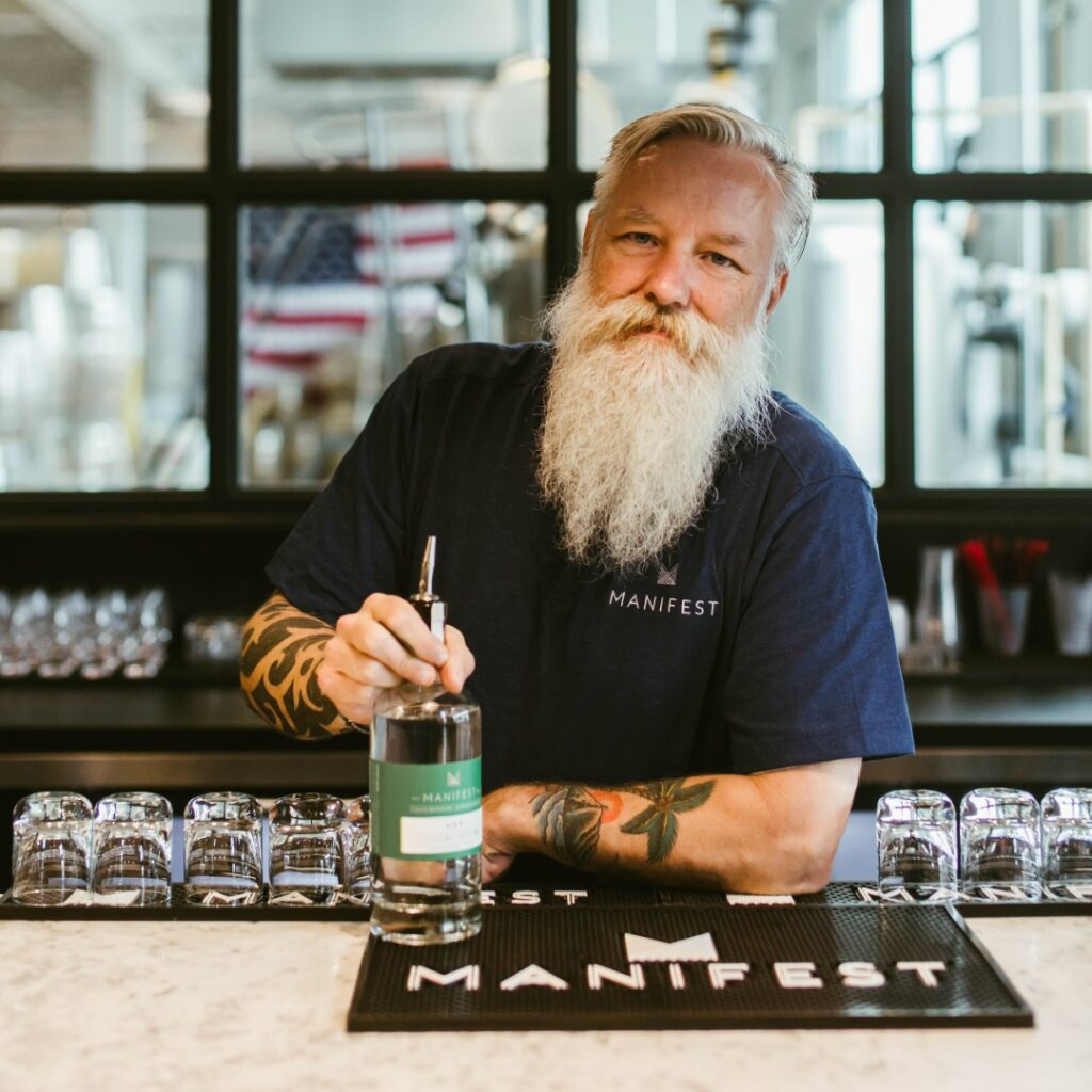 Jim Webb leans on the bar holding a bottle to make a drink. He has a long white beard, tattoos on his forearms and wears a Manifest T-shirt.