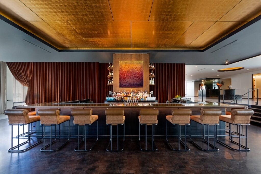 A picture of the Flor Fina bar in Central Florida. A metallic ceiling shines above the square bar with sturdy seating.
