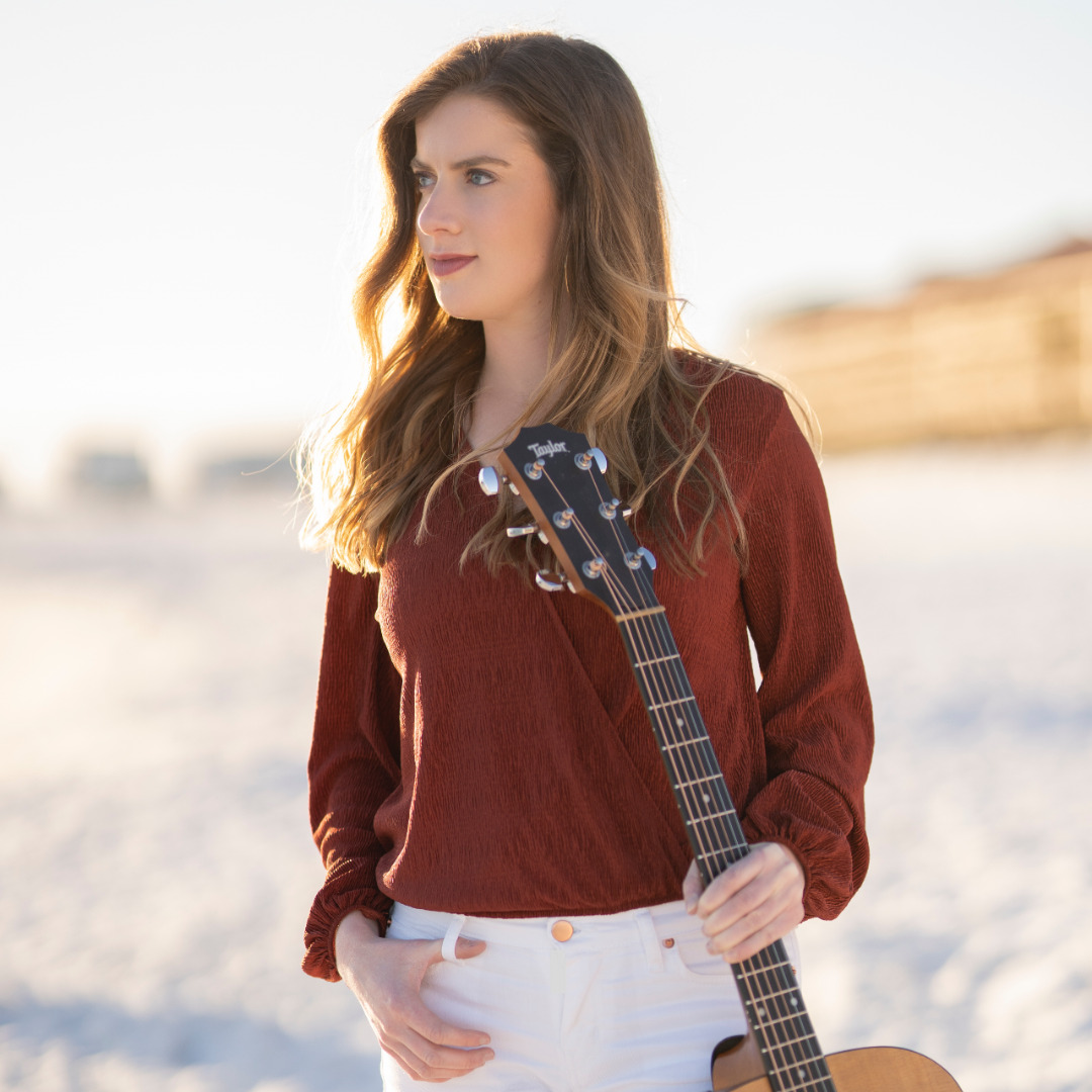 Allison Clarke stands on the beach in a rust top holding her guitar.