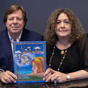 Ron Sachs and Gay Webster-Sachs sit with their book The Secret in the Clouds, which has a blue cover and cartoon illustration of a girl and unicorn.