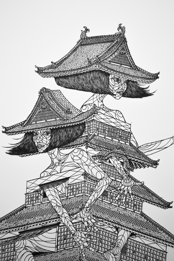 A paper cutting of two woman emerging from a castle. They wear the roofs as hats.
