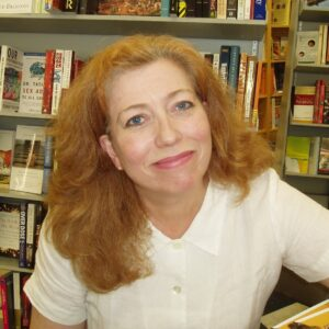 Diane Roberts sits in front of a bookshelf.