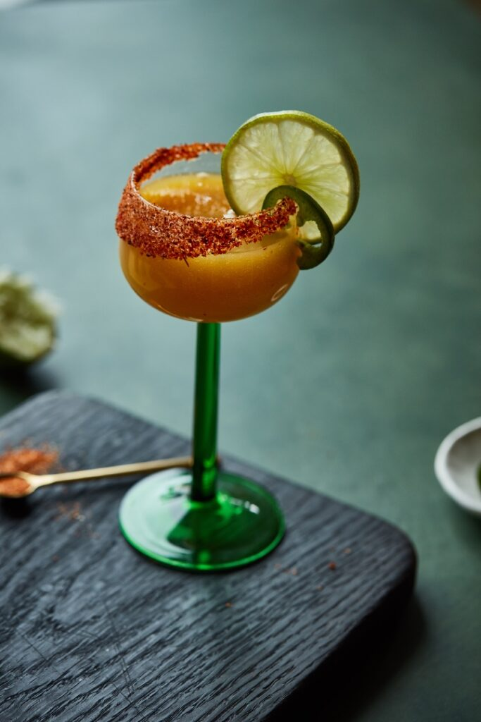 A mango margarita in a glass with a tall green stem and adorned with a spice-coated rim and lime wheel.