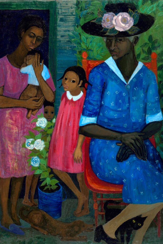 A portrait of three generations of women. A mom holds a baby. A child peaks over a plant. A young girl in a dress stands in the middle. A grandmother sits in a chair to her left.