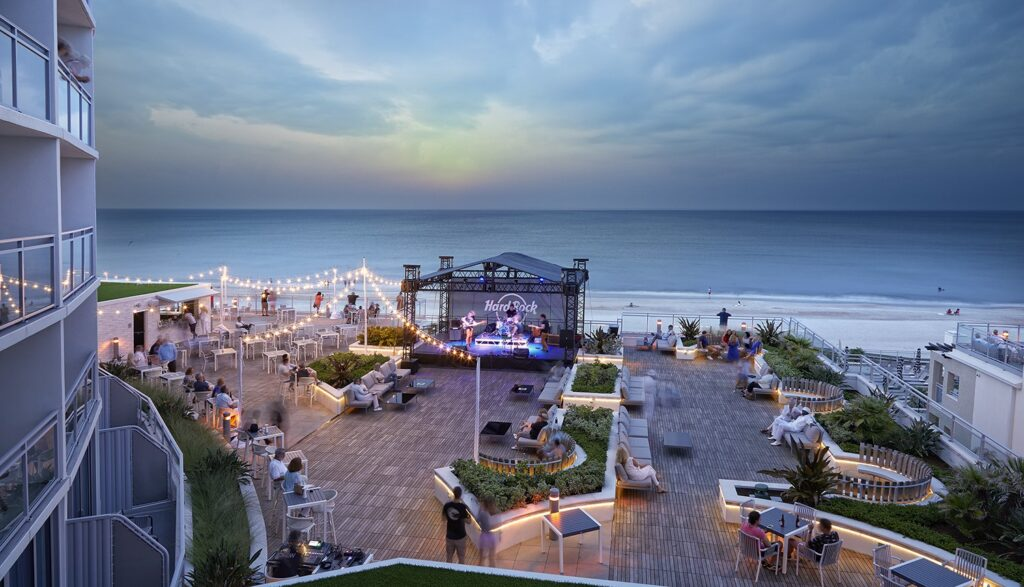 An outdoor patio at the Hard Rock Hotel Daytona Beach. You can see the beach, tables and a Hard Rock stage.