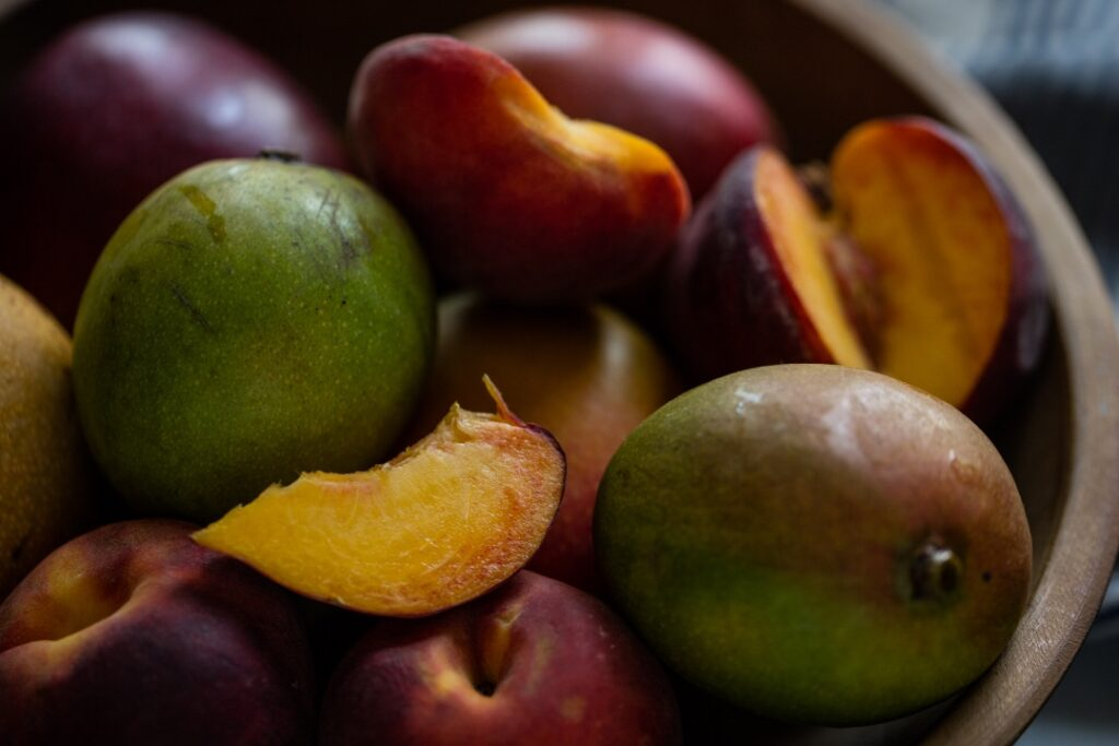 Mangoes in a bowl. Some are sliced. They are various shades.