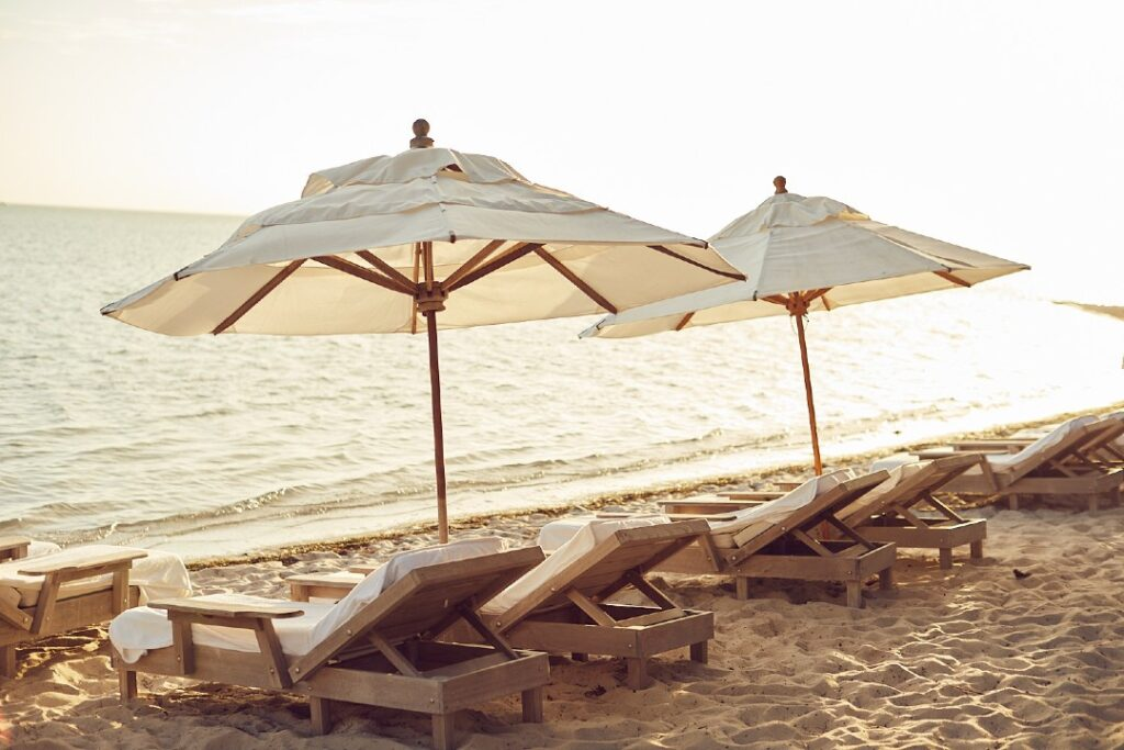 Lounge chairs and umbrellas sit in the sand along the shores of Little Palm Island.