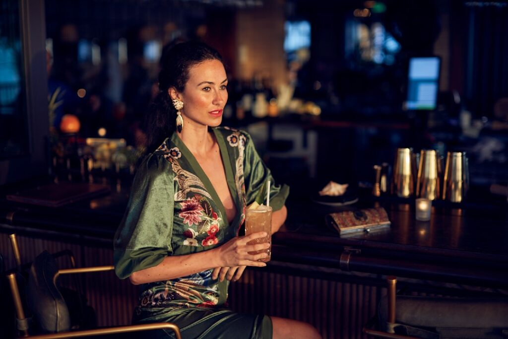 A model sips a cocktail. Her hair is pulled back and she wears a green kaftan. She is well-lit against a moody atmosphere.