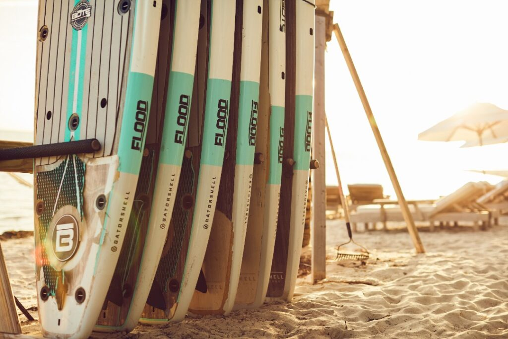 A stack of six surfboards is in a rack on the beach.