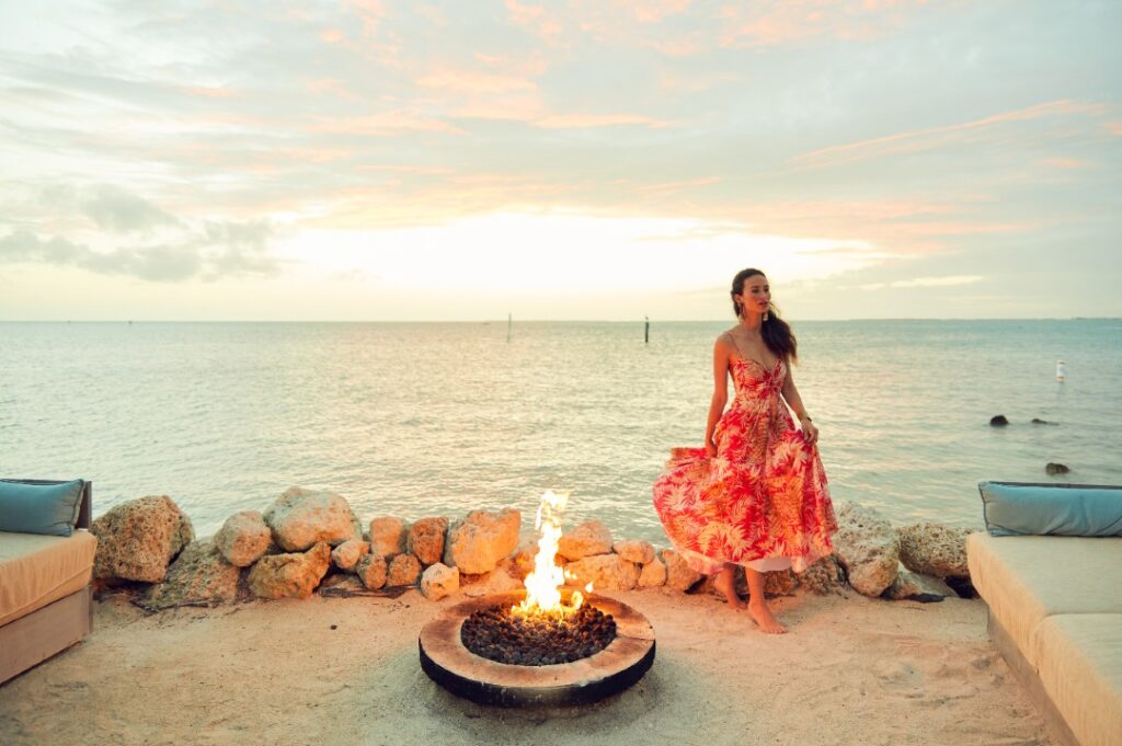 A model wears a red dress and poses against a pink and blue sky. It is sundown and a fire burns in a fire pit overlooking the horizon.