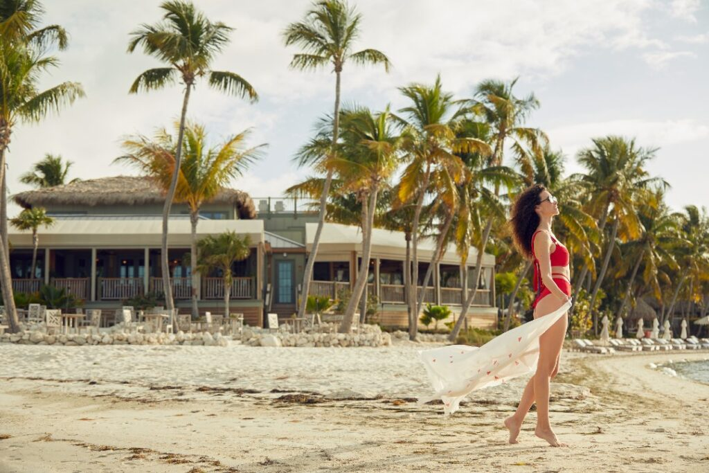 A model stands in the sand on Little Palm Island. In the background are one of the resort's buildings and lots of palm trees.