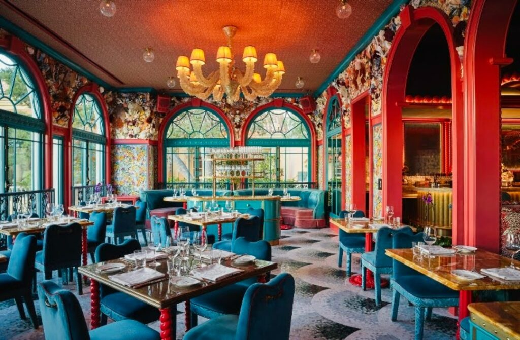In an Art Deco-inspired restaurant, there is a large chandelier, teal arched windows, salmon trim, and teal seating. The walls around the arched windows are covered in Wilm's shelled panels.