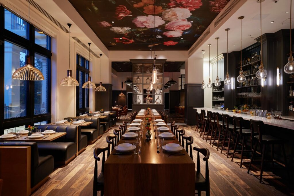 Ovide is a new North Florida restaurant in Hotel Effie. In this photo, the restaurant's booths and long table are visible. There is a floral mural on the ceiling and a moody atmosphere.