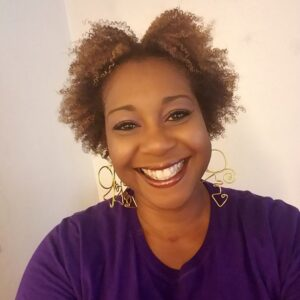 Yolanda Franklin smiles at the camera. She wears big, gold earrings and a purple top.