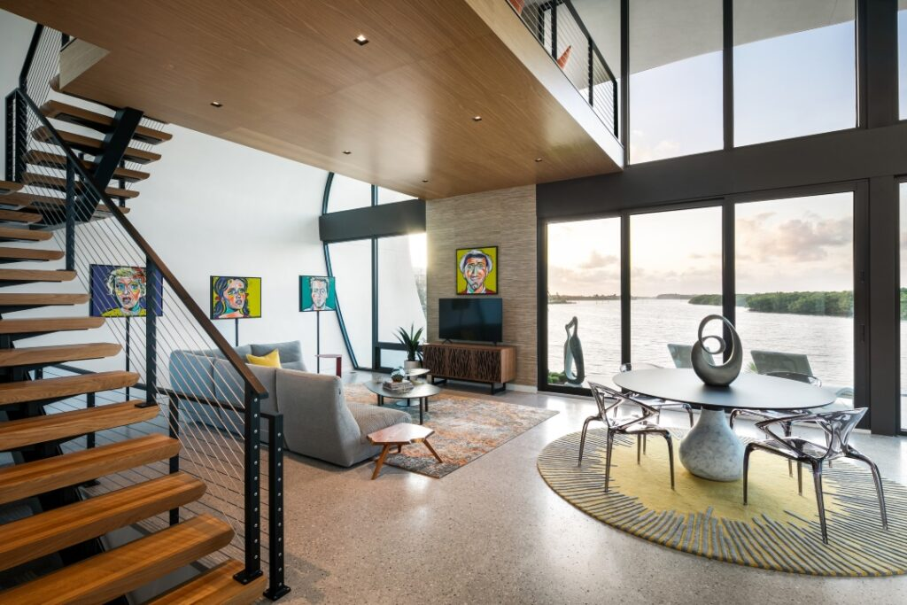 In this photo of the living space, you see a warm wood staircase with a modern railing with cable railing. Concrete or terrazzo floorings stretches out across the space. A living room is anchored by a rectangular rug with a couch facing the TV, windows and colorful artwork. A circular dining table sits on a circular rug.