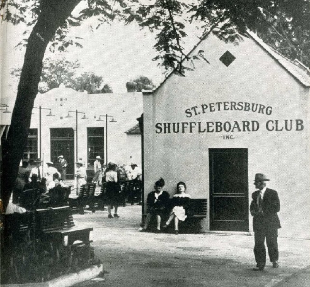 In this black and white photo, two women sit on a bench against the St. Petersburg Shuffleboard Club building. A man in a suit and hat walks by in the foreground. In the background, dozens of players gather at the courts to play shuffleboard.