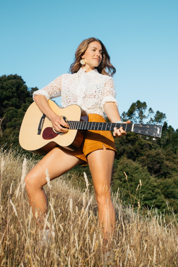 Caroline poses looking away from the camera while in a field holding her guitar. She wears a white blouse and orange shorts.
