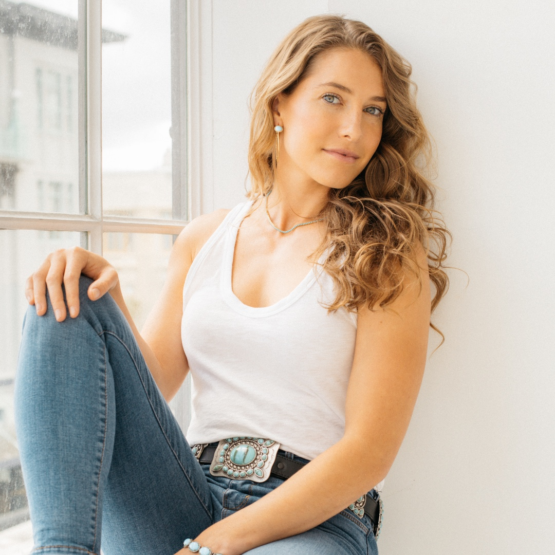 Caroline poses in a window wearing a white tank top and jeans. She leans against the wall, and she looks slightly over her left shoulder at the camera.