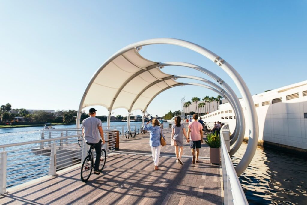 People bike and walk down the Tampa Riverwalk with its wooden pathway and arched shade overhead.