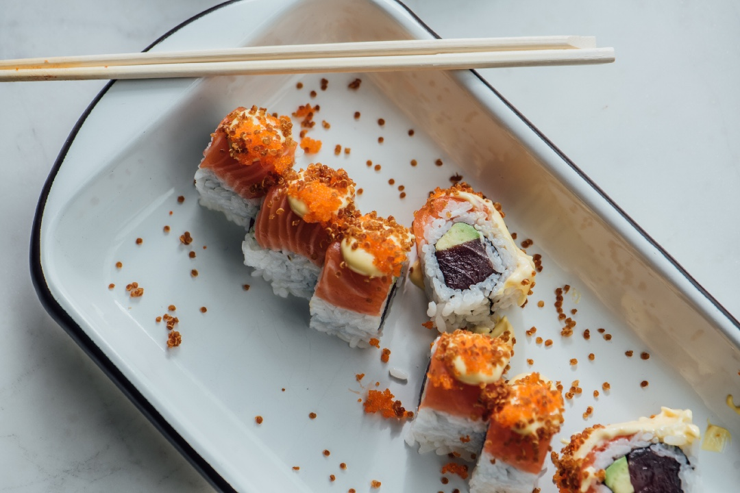 Seven sushi rolls are visible in the photo with one cut off and another tipped on its side in the center. Beet-reddish tuna and fresh avocado make up the center of the roll and quinoa is sprinkled on top.