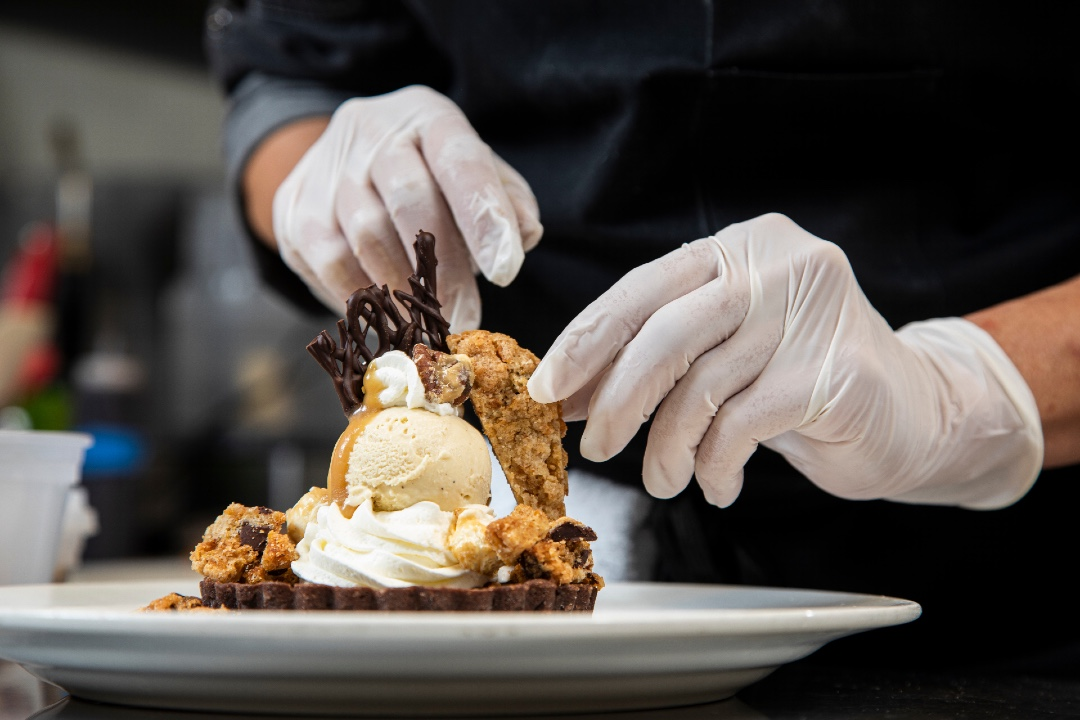 Gould, pastry chef at the Kool Beans restaurant in Tallahassee, tops the dessert of chocolate mousse base with a perfect scoop of salted caramel gelato with the tasty garnishes.