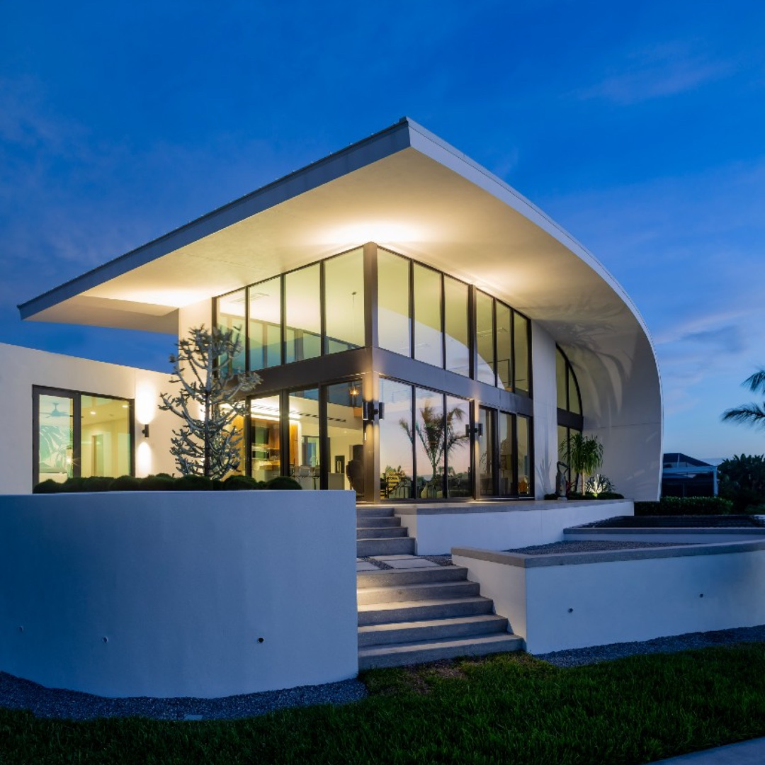 A photo of a white home with sculptural design. It is dusk and the house glows against the sky.