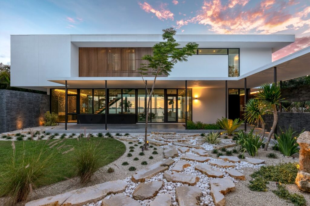 In this photo of a home designed by Sweet Sparkman, a courtyard with stone stretches out from a modernist home with many glass windows and boxy shape. The architecture features  limestone walls.