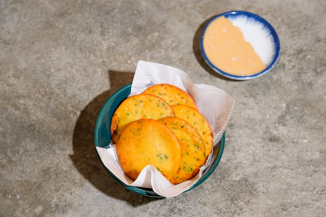 Circular corn fritters sit in a blue dish with a side of dipping sauce.