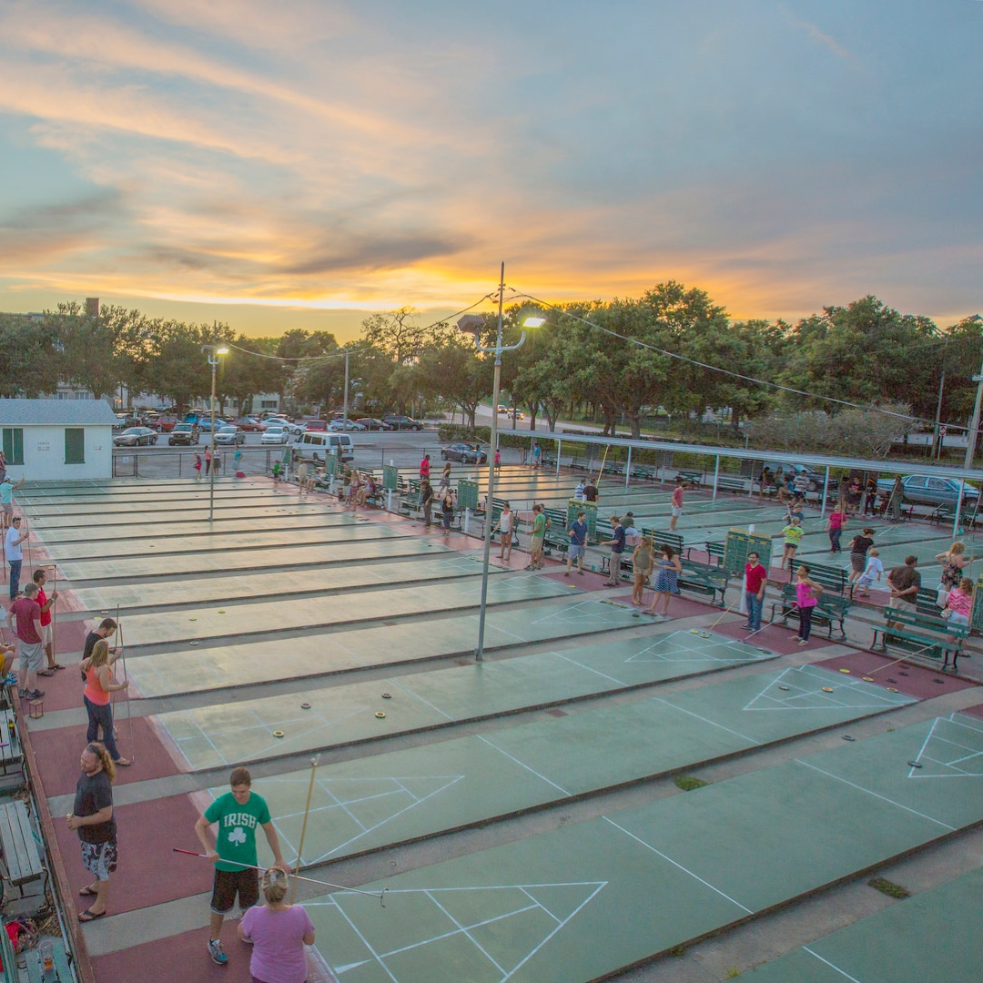 ns of players of all ages gather around the shuffleboards at the St. Petersburg Shuffleboard Club. It is sunset.