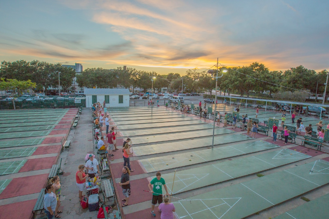 In this wide shot, dozens of players of all ages gather around the shuffleboards at the St. Petersburg Shuffleboard Club. It is sunset.