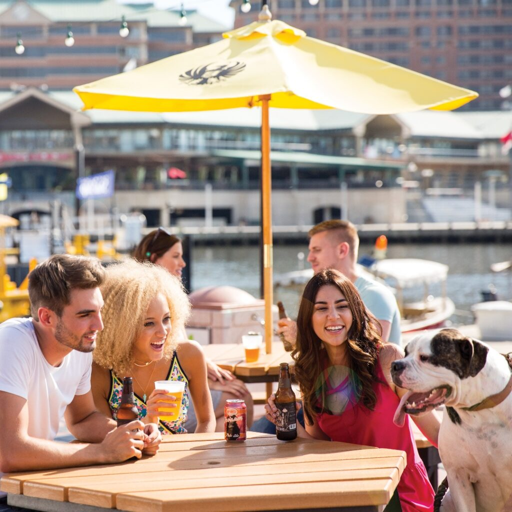 A group of three and their dog sit with drinks at an outdoor, waterfront table at Sail Pavilion.